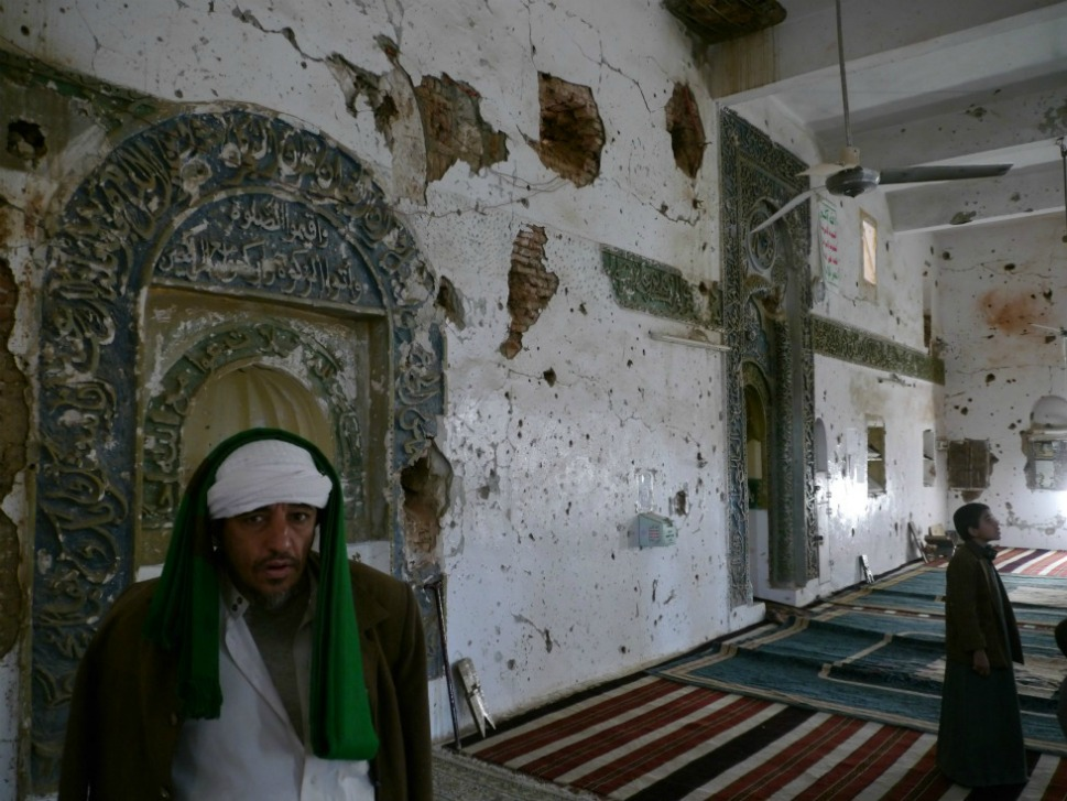 """A  Zaidi imam,  his prayer mat draped across his head, surveys the bullet-pocked interior of an  ancient mosque in the old city of Saada. """"Allah is Great, Death to America,  Death to Israel, Damned be the Jews, Victory to Islam,"""" reads the Houthi's  brazen slogan, written on the wall of the mosque. The mantra can be found  stenciled on billboards, houses and mosques across the city."""