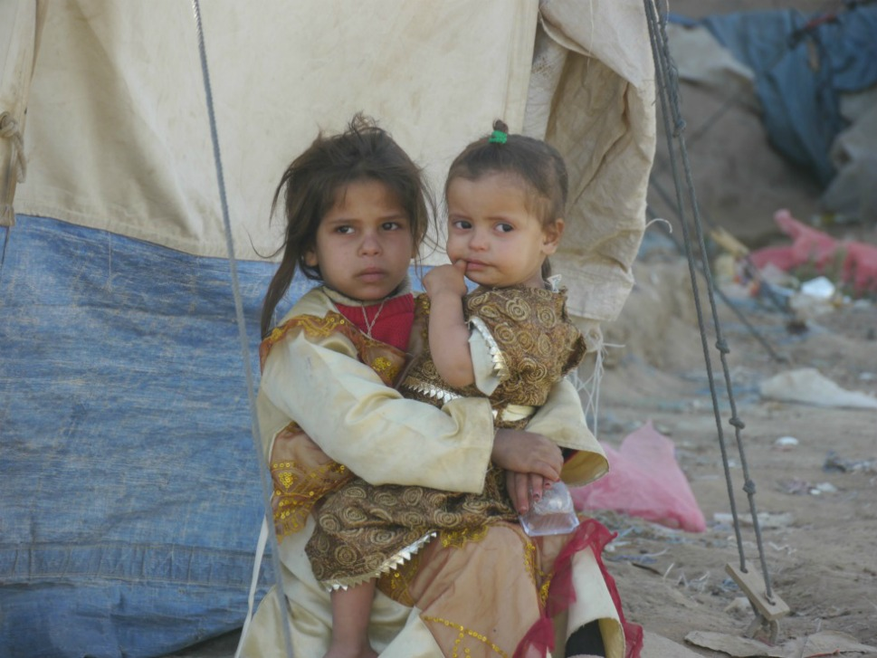 A  girl cares for her sister in a threadbare camp for displaced Yemenis in Saada  city. In early 2011, more than a year after a January 2010 ceasefire between  Houthi rebels and Yemeni and Saudi forces, more than  250,000 internally displaced people (IDPs) remained scattered across Yemen in  protracted displacement.