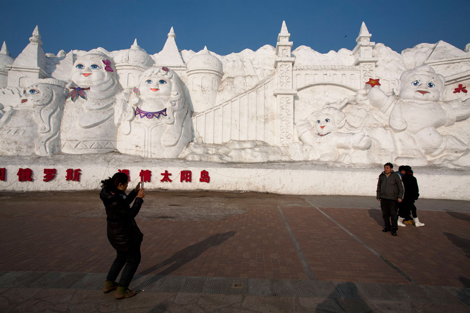 A snow sculpture within the ice city depicts a fairy-tale scene.