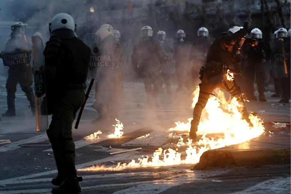 A riot policeman is set ablaze by a gas bomb during  the clashes.