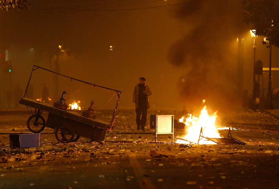 A lone man walks through the rubble of the burning square.