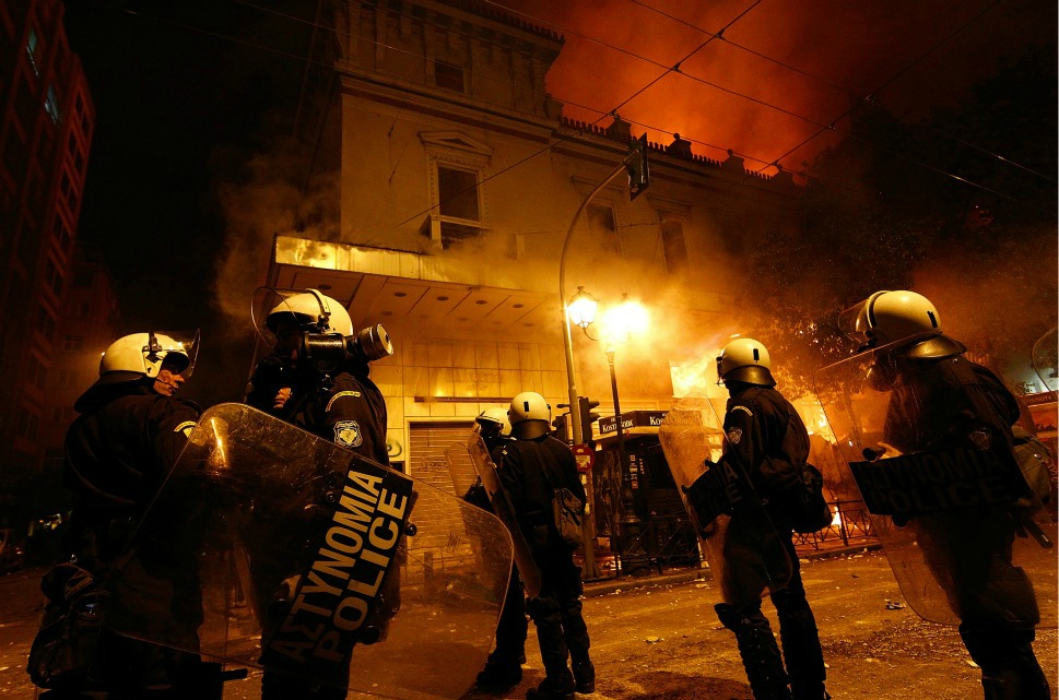 Special police forces stood guard as firefighters put out  a blaze on Stadiou Street during the demonstration.