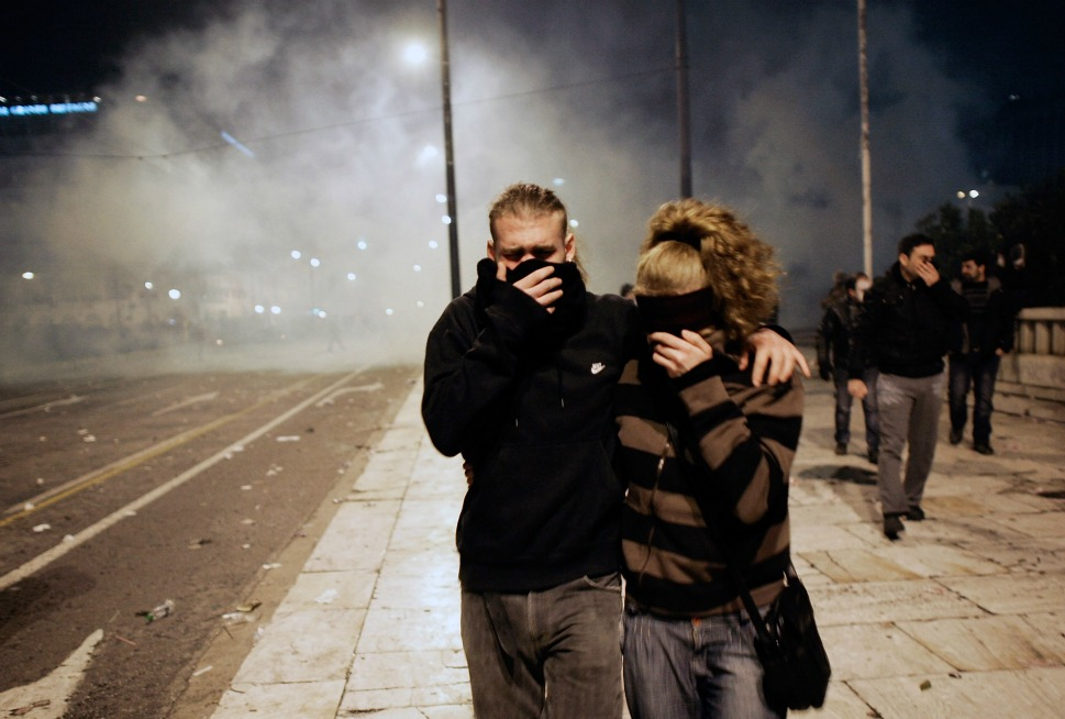 Demonstrators try to protect themselves from tear gas.