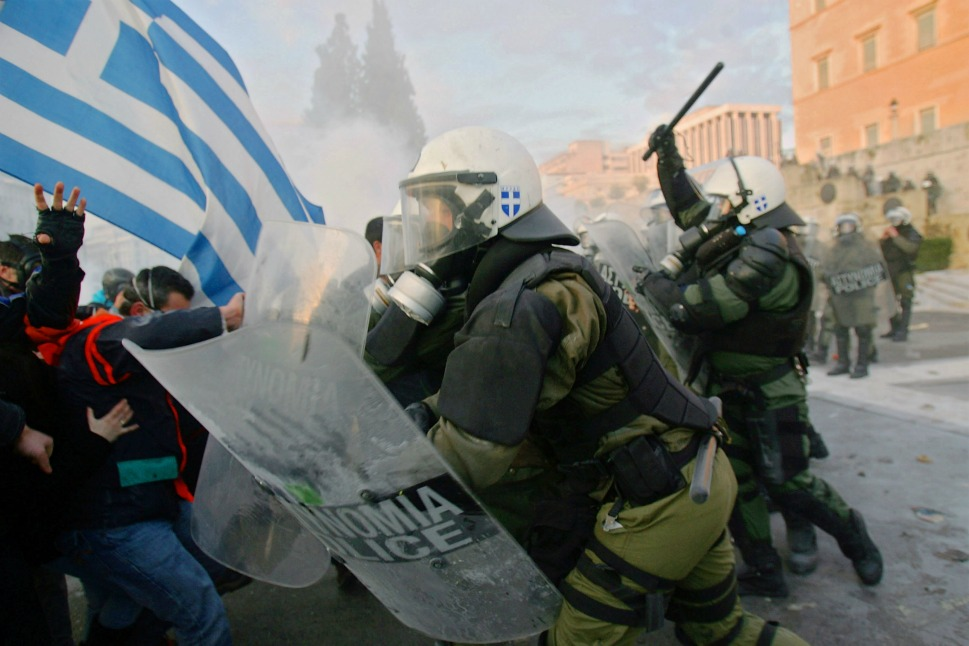 Thousands of demonstrators clashed with police as the Greek parliament prepared  to vote.