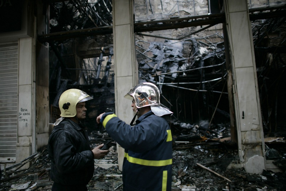Firefighters attended to a burned out building on Feb. 13, the morning  after violent protests against the government's austerity plans.