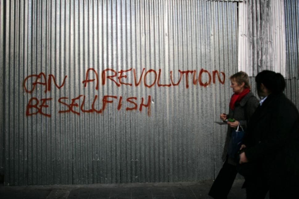 Pedestrians walk by protest graffiti.