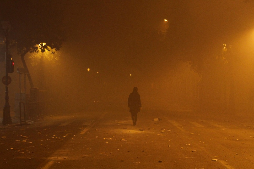 A girl walks through a smoke-filled area in downtown Athens on Feb. 12.