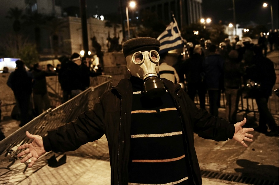 A protester wearing a gas mask poses for a photograph  during clashes with riot police.
