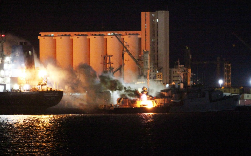 Fire engulfs a boat in the  port of Tripoli after NATO aircraft hit eight vessels belonging to Qaddafi's  navy in the early morning hours of May 20, 2011.