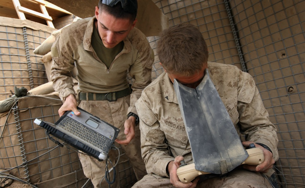 U.S. Marine Sgt. Nicholas  Bender and Lt. Cpl. Dennis Goddard monitor the flight of a Raven surveillance  drone from a Marine base on March 21, 2009, near Baqwa.