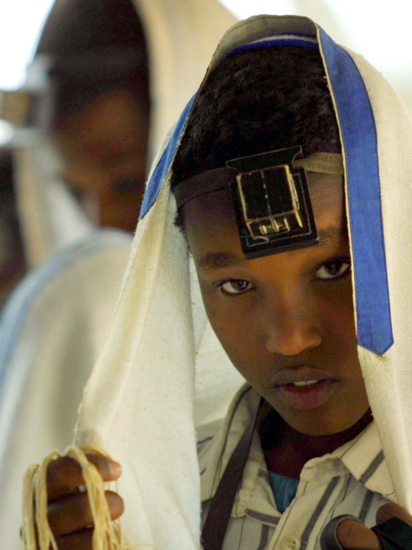 """A teenage Ethiopian Jew with his tahlit and teffilin, at the Beta  Israel School March 14, 2003, in Addis Ababa, Ethiopia. The Israeli government airlifted more  than 22,000 Ethiopian Jews to Israel in 1984. Satisfied that all qualified  Jews had left Ethiopia in the airlifts, the Israeli government then closed down its  offices in Addis Ababa in 1991. However, in recent years, a number of Jews who were left  behind or have had children since -- up to 17,000 people -- have moved from their villages to Addis Ababa and are waiting for the  Israeli government to accept them under the """"Law of Return."""" For reasons that include a limited paper trail  authenticating their Jewish identity, conversions to Christianity by  grandparents, or a reluctance on the part of Israel to accept more Ethiopian  refugees, these Jews have lingered around in compounds, waiting  indefinitely to return to Israel."""