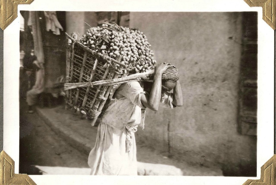 To distribute oil wealth throughout its small population, the Kuwaiti government began buying real estate in the city center from locals at vastly inflated prices, then moved inhabitants to newly built suburban developments. Ambitious development projects were then begun along the harbor.      Above, a man transports dates in a large basket.