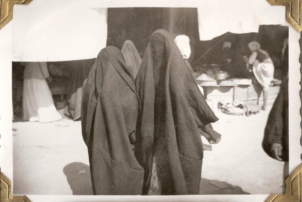 Women walk through the city market in 1950.