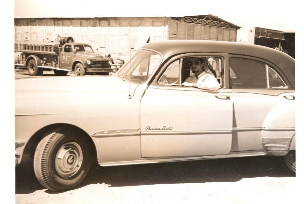 An unknown man sits in a first-generation Pontiac Eight.