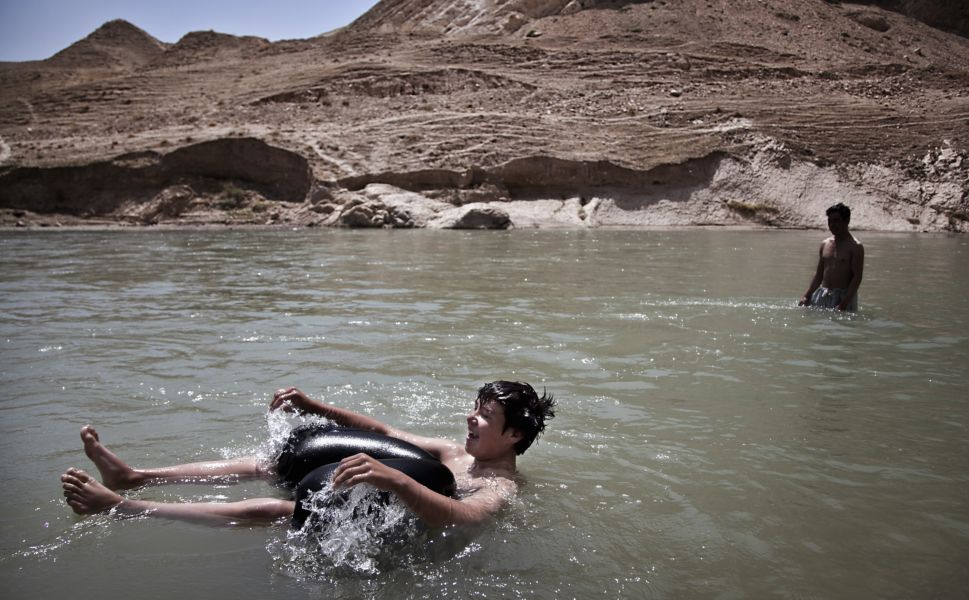 A boy inflates his baggy  pants as an improvised flotation device while swimming in the Balkh River trying to beat the Ramadan heat.