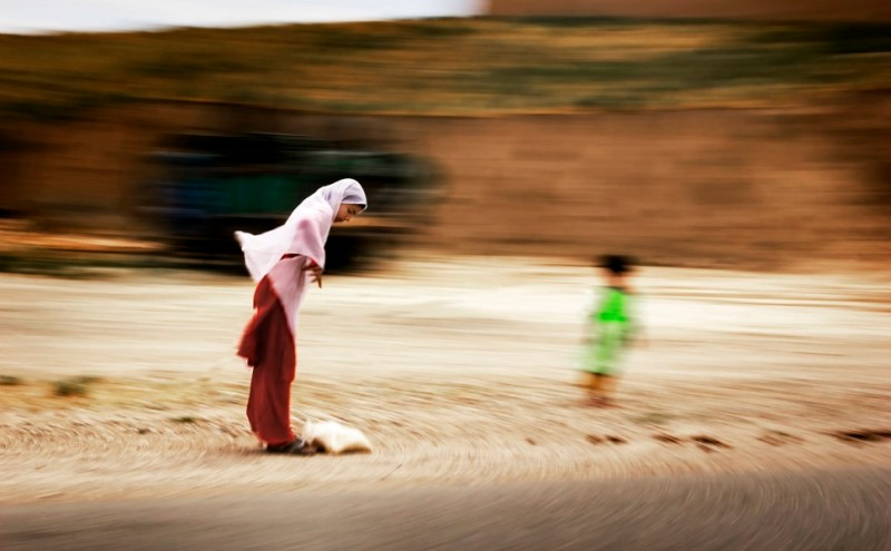 A young girl pauses to adjust  her scarf on a windy day on the road between Kunduz and Mazar-e-Sharif.