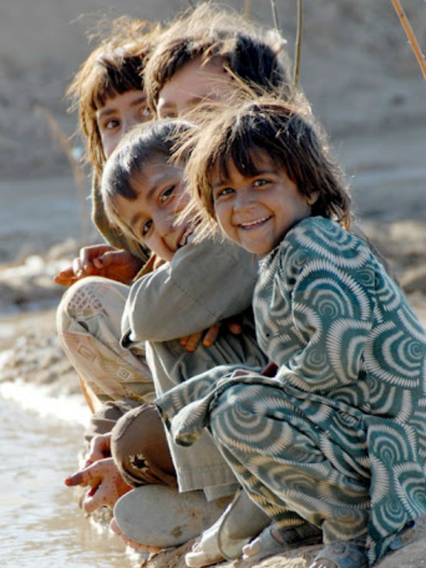 Child's play: Children from a village near  Quetta smile for a picture alongside a stream. Large families are the norm in  Baluchistan: The average family size in a poor household is eight people, the  majority of whom receive little or no education. According to the director of a recent documentary on the subject, nearly 80  percent of child laborers in Pakistan are 14 years old or younger.