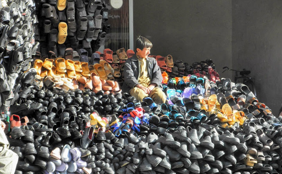 A mountain of shoes: An Uzbek boy sits atop a heap of  locally produced and Iranian shoes in one of the most crowded bazaars of the  city. Boys as young as 10 years old work alongside their fathers -- and  sometimes by themselves -- to support their families.