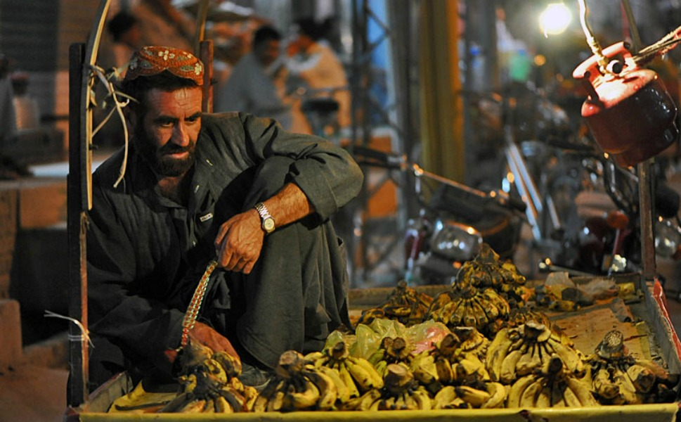 The fruit basket of Pakistan: A Pashtun fruit vendor sells  bananas on a wheeled cart in a Hazara neighborhood. For some fruit vendors, the  cart serves as source of livelihood, as well as part-time shelter during forays  into the city center, far from home. On a good day, a fruit vendor could earn  up to $10.