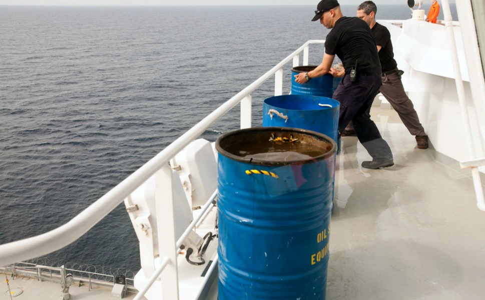 SeaGull security members adjust barrels filled with water on the wing of the boat in order to  protect the bridge from bullets.