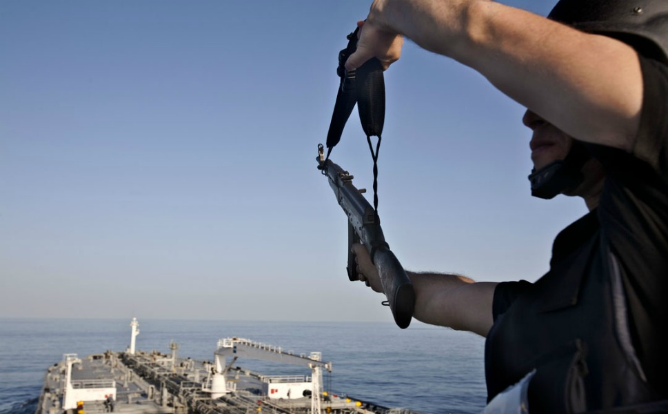 A SeaGull security-team member waves his weapon in the air as dew skiffs (small engine boats used by pirates) get within a range of  1.5-2 miles from the tanker. The gesture is meant to make the pirates understand that there is a security team onboard the tanker, hopefully discouraging attacks.