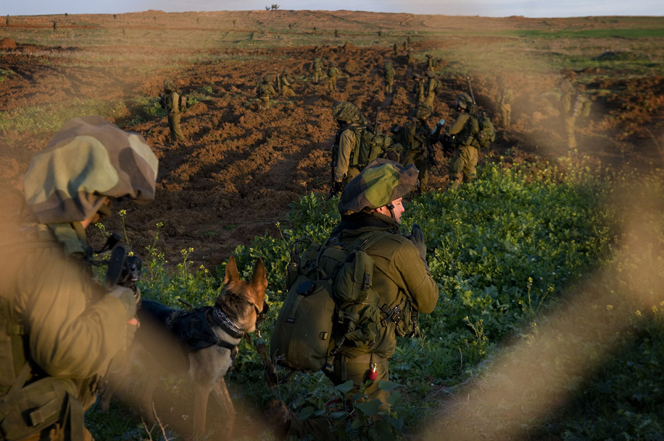 """The dogs that make up Israel's elite canine fighting force, Oketz  (the Hebrew word for """"sting""""), are especially hardcore. The Israel Defense  Forces (IDF) use three breeds -- Belgian, German, and Holland Shepherd --  and all have a reputation for being highly trained, relentless, and fierce  attackers. The canine program, though  finally made public in 1980 after years of operation in the shadows, is still extremely  secretive about the details of its operations. As one Oketz commander told  Haaretz: """"Our dogs know how to  spare civilians and home in on terrorists. How do they? That's our  secret.""""      When choosing its handlers, the IDF is highly selective. The tryout session alone lasts three days. As  one handler who made the cut said, """"220  soldiers show up to the tryouts and only 30 pass."""" During a training period  that lasts for upwards of 17 months and includes both basic and advanced  infantry instruction, the handlers and their canines are taught to work with  every """"unit in the army,"""" learning everything from parachuting to urban  warfare to counterterrorism.      The Oketz dogs have sparked controversy  in the past. In March, a patrol dog bit  a Palestinian protester during a demonstration in the West Bank. The man was  only """"lightly hurt,"""" according to Haaretz.      Above, Israeli infantry soldiers enter Gaza on  January 4, 2009, on the border between Gaza and Israel.      Shaul Schwarz/Getty Images"""