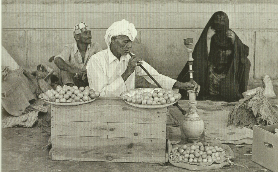 A man selling dried herbs and lemon pauses to smoke a pipe.