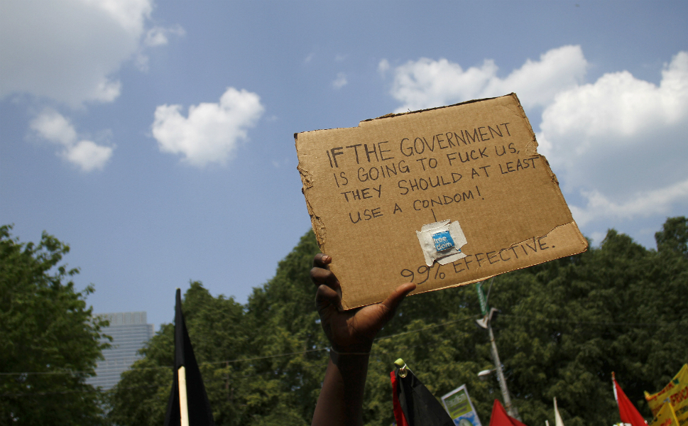 A demonstrator holds a sign expressing general displeasure with the U.S. government at the summit meating on May 20.
