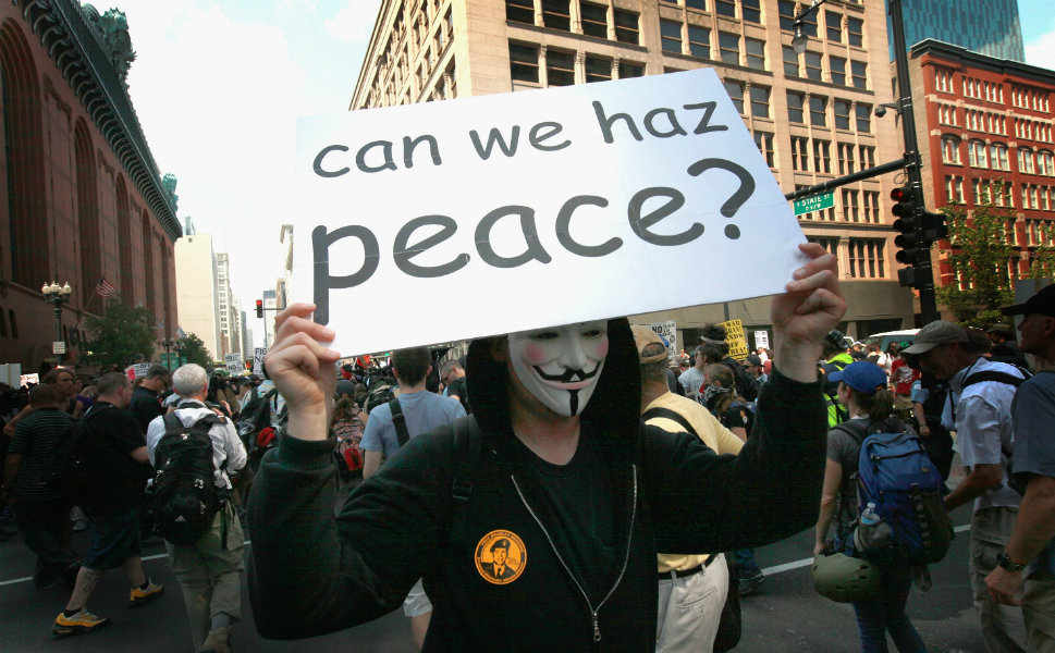 A masked protestor marches in downtown Chicago holding a sign referencing a popular Internet meme.
