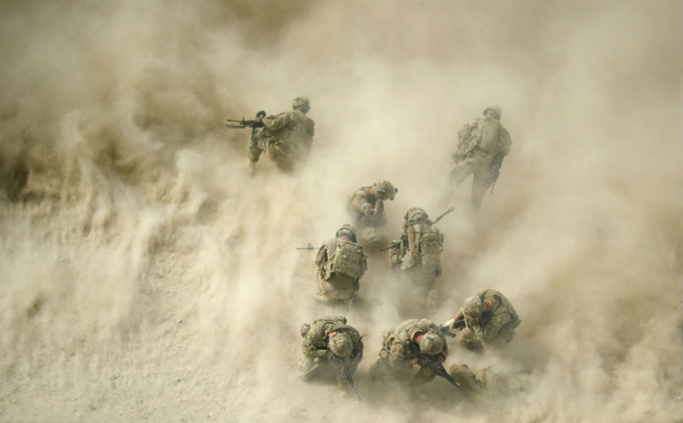 U.S. soldiers gather near a destroyed vehicle and  protect their faces from dust blown by a helicopter -- known as rotor wash -- as their wounded comrades are airlifted by  Medevac from the 159th Brigade Task Force Thunder to Kandahar  Hospital Role 3. Three soldiers were wounded while their  vehicle was destroyed up by an improvised explosive device.