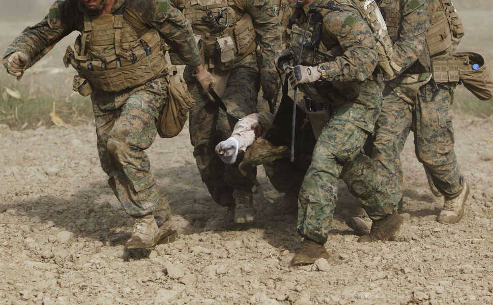 Seen through a haze of fine dust kicked up by a  helicopter's rotor blades, U.S. Marines carry a wounded comrade who was hit by an improvised explosive device to a medevac helicopter of U.S. Army's Task  Force Lift 'Dust Off' Charlie Company 1-171 Aviation Regiment in Helmand  province on Nov. 2, 2011. The marine lost his right leg from the knee down in  the blast.