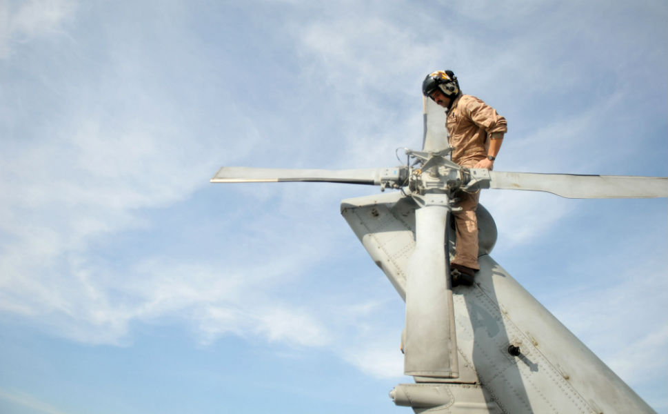 Lt. John  Coombs, assigned to the Warlords of Helicopter Anti-Submarine Squadron Light  51, conducts preflight checks before flying with members of the humanitarian  assessment survey team to assess the damage caused by flooding on Oct. 22, 2011  in Bangkok, Thailand.