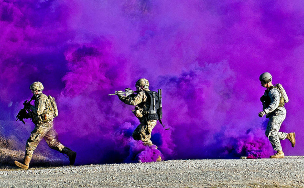 Three paratroopers with the 82nd Airborne Division's  1st Brigade Combat Team and a trainer run through a smokescreen during a  live-fire exercise on Jan. 14, 2012, in Fort  Polk, Louisiana. The middle soldier carries several tools used to breach  doors on his back.