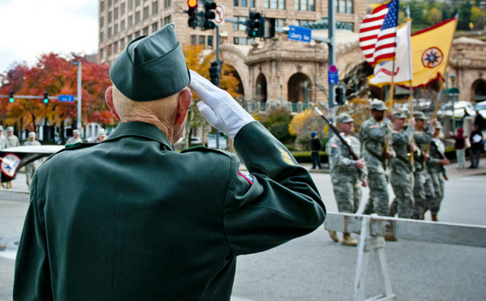 Retired Army 1st Sgt. William Staude, of Elliott,  PA, salutes the colors being carried by soldiers from the 316th Expeditionary  Sustainment Command as they march past him  during the Veterans Day parade in downtown Pittsburgh on Nov. 11, 2011.