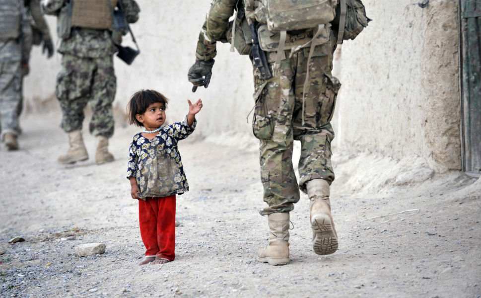 An Afghan girl greets a joint patrol of U.S. troops  from the Charlie Company, 2-87 Infantry, 3rd Brigade Combat Team at Kandalay village in the southern Afghan province of  Kandahar on Aug. 8, 2011. U.S. troops had just launched missile attacks on Taliban  targets in nearby Kelawai village, killing at least three and capturing two  insurgents.