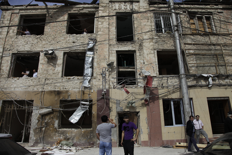 Locals survey a damaged  building on one of the central streets in Makhachkala, after three car  bombs, believed to be the work of the insurgency, ripped through a major city  block on Sept. 21, 2011, wounding 50 people and killing six.