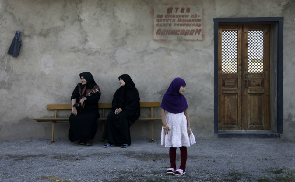 A young Dagestani girl stands in front of her  family.