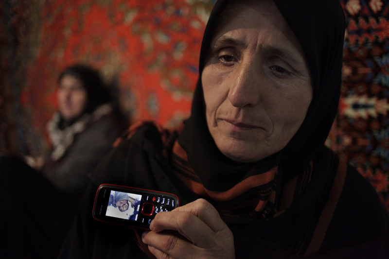 Khadizhat Nasibova holds up  a mobile phone with a picture of her son, Magomed Nasibov, 21, displayed on the screen. He died in July of 2010. Nasibova says she witnessed the murder of her son and nephew by men in camoflauge not far from her home in the small village  of Kirov-al-ul.
