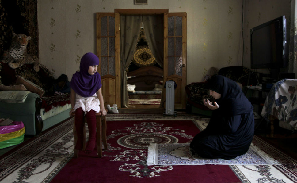 Achalimova prays at home as her  daughter looks on.