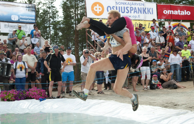 """12. Eukonkanto (Wife Carrying)      This  sport was originally inspired by the 18th-century legend of Herkko  Rosvo-Ronkainen, a Finnish forest thug who stole women from villagers. While  that charming practice is generally frowned upon these days, it's morphed into  the sport of wife carrying. The first """"Wife Carrying Championship"""" was held in  the town of Sonkäjarvi in 1992. Most competitors use the """"Estonian style""""  technique, wherein spouses hang upside-down on their husbands' backs, grabbing  hold of their waists, while the men race through a 253.5-meter course, peppered  with log hurdles and water obstacles. The prize? Beer, of course. The sport has  grown rapidly in Finland and spread to parts of the United States, with  annual competitions now organized in Maine, Wisconsin, and Michigan."""