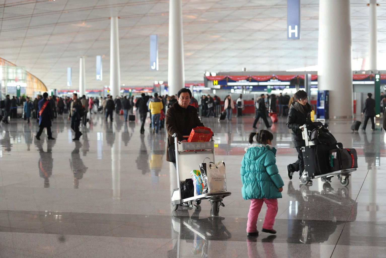 Beijing: With the opening of its third airport by 2015, Beijing is expected to surpass  London as the world's busiest air hub. Beijing Capital International Airport's  Terminal 3 is already larger than all five terminals at London's Heathrow  combined. Above, passengers walk through a terminal at Beijing's Capital airport in January 2011.