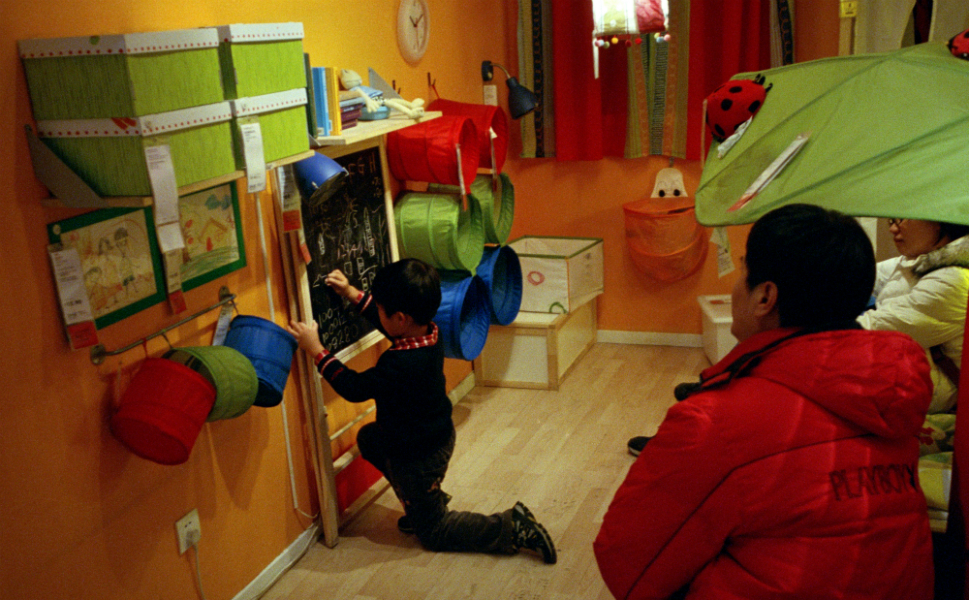 Parents watch their son draw Chinese characters on a small  blackboard in a child's room.