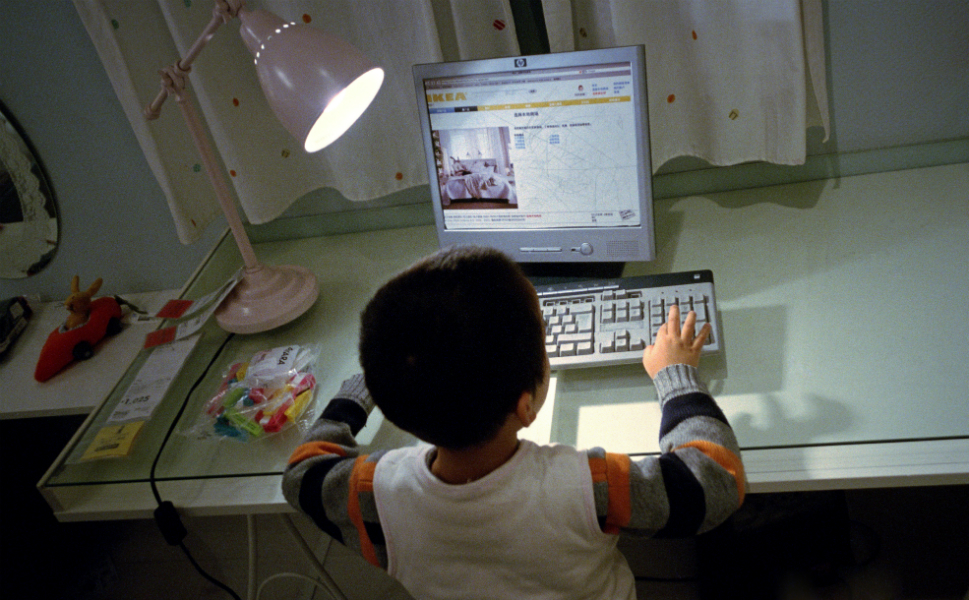 A young Chinese boy plays on a fake computer.