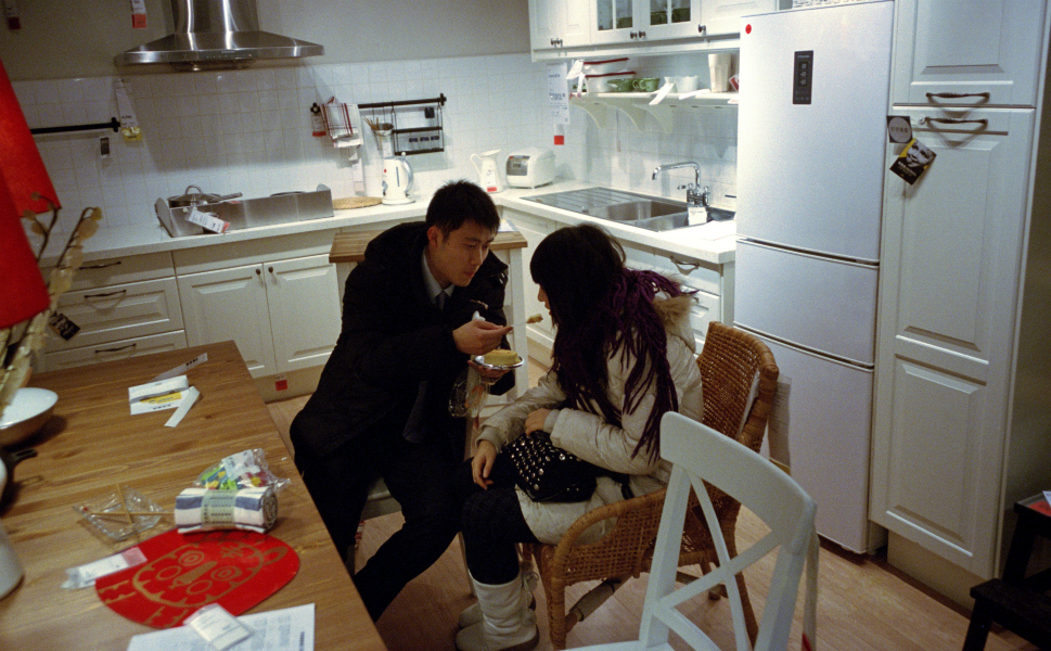 A couple shares a snack.  Ikea's flagship store in Beijing received more than 6 million visitors in 2011, the most of any Ikea store in the world.