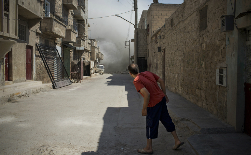 A man peers down  a street as smoke and dust rises from a residential home destroyed by a bomb dropped from  a Syrian fighter jet on Aug. 6. Eleven civilians from two  families died, including at least four children.