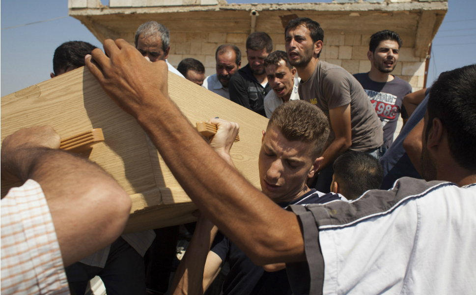 FSA fighters and family members carry the coffin of Omar Ismail Abdul Rahman,  30, to his burial in Tal  Rifaat, in Aleppo province, on Aug. 9. Omar, a young farmer from northern  Syria, took up arms against the government and was killed fighting on the front  lines of the Saluheddin neighborhood in Aleppo.