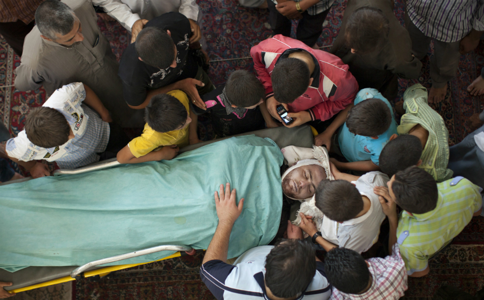 FSA fighters and family members grieve over the body of Ayman Alito -- who also died  fighting for the FSA in the Salaheddin neighborhood -- in a mosque in Tal Rifaat on Aug. 9.