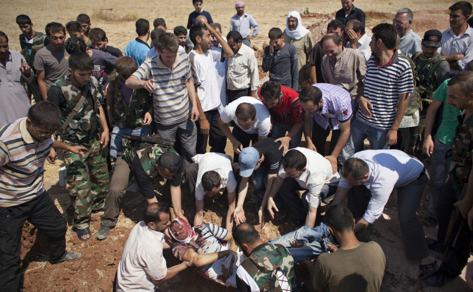 FSA fighters and family members lower Abdul Rahman into his grave in Tal  Rifaat on Aug. 9. He was buried in his hometown near the fields he  worked in before the revolution.