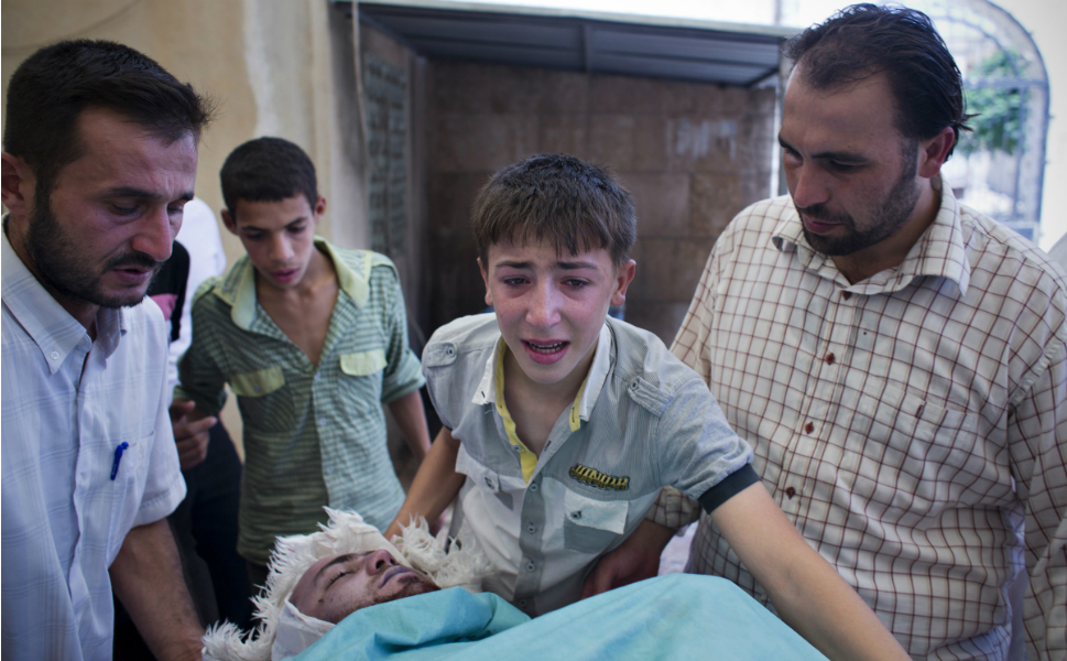 A boy grieves over the body of Alito as they take his body to the mosque  in Tal Rifaat on Aug. 9.