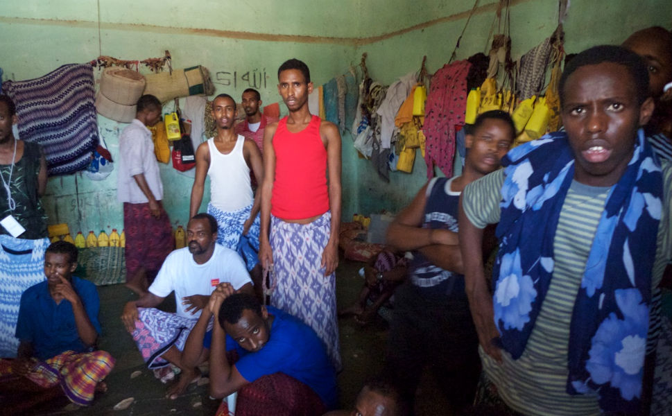 """While the PMPF did make gains against piracy, the threat of a resurgence looms large in Puntland. Above, some of the more than 400 pirates held in the Bosaso town jail pose for a picture. Pelton reports, """"In 2012, I met children as young as 12 being held for piracy. Many of the pirates are reformed or have their sentences reversed on 'appeal' after a financial payment is made. The Somali legal system is influenced by the traditional 'xeer,' which works to negotiate an acceptable solution to defuse tensions and resolve clan-based disputes. Families of jailed pirates can appeal to this system and often pirates are released after serving a nominal sentence."""""""